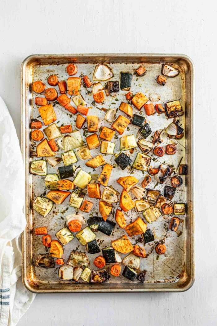 Roasted sweet potato, onion, carrot and zucchini on a baking tray.