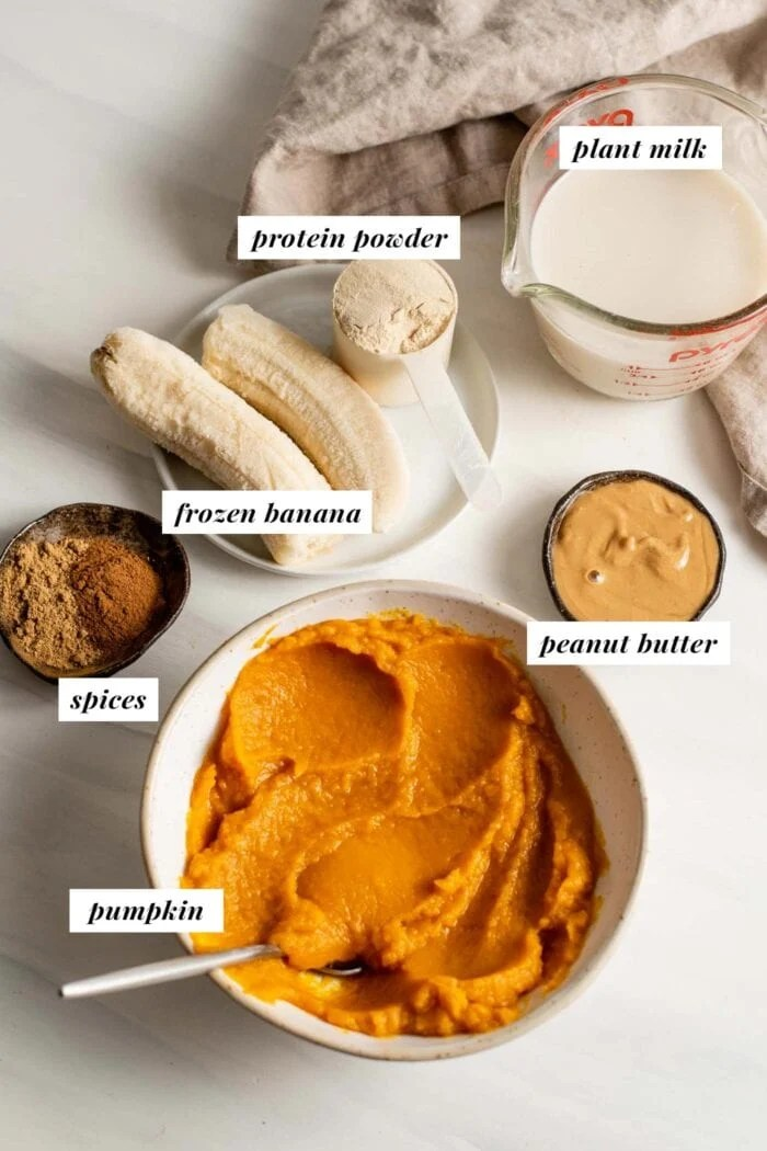 Labelled ingredients in bowls for making a pumpkin and peanut butter smoothie.