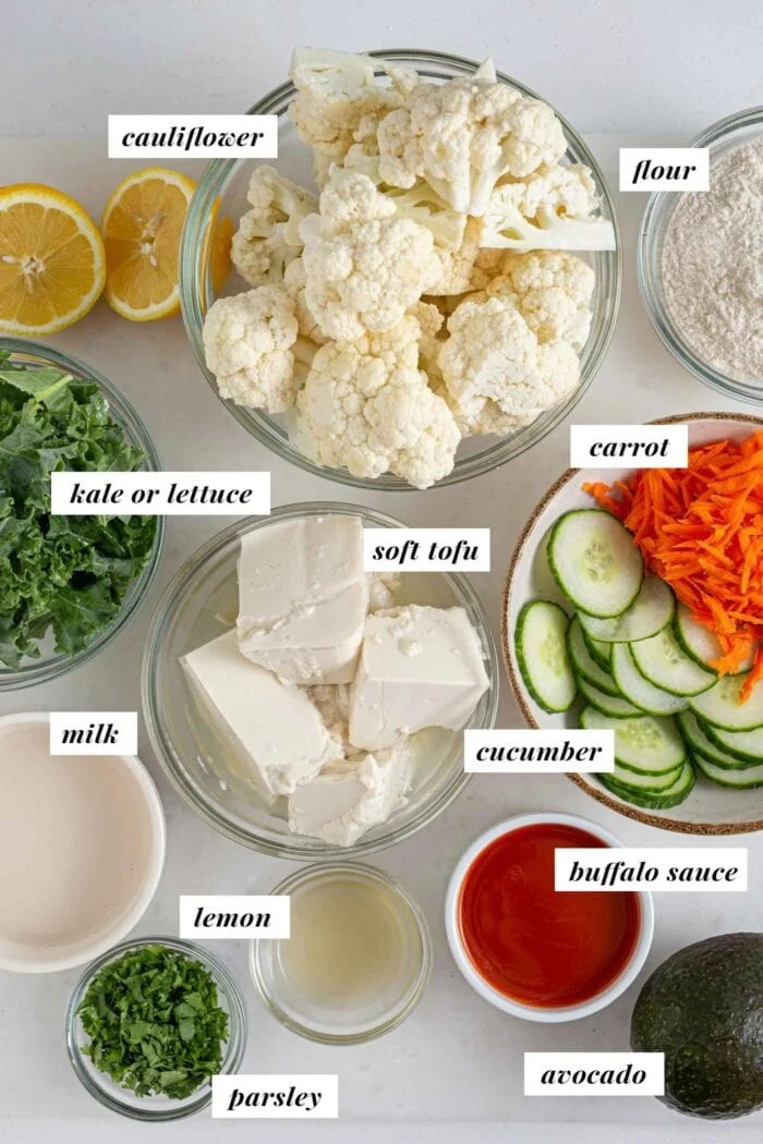 Labelled ingredients for making a buffalo cauliflower wrap with avocado, kale, cucumber and carrot.
