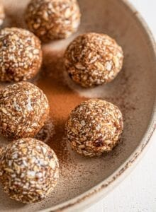 Plate of oatmeal energy balls sprinkled with cinnamon.