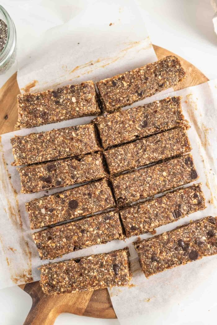 12 sliced energy bars on parchment paper on a cutting board.