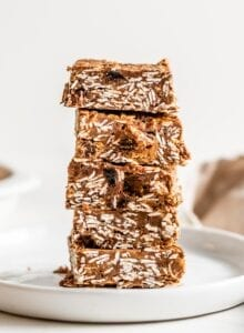 Stack of 5 chocolate oat bars on a plate. More bars in background.