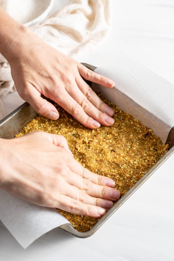 Two hands pressing dough into a parchment paper lined square baking tray.