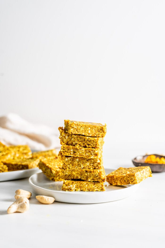 Stack of 6 turmeric coconut and cashew energy bars on a small plate. More bars in background. Cashews scattered about.