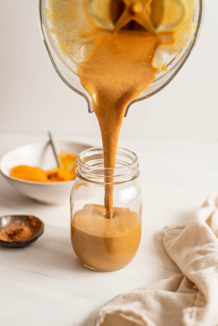 Blender pouring a pumpkin smoothie into a glass jar.