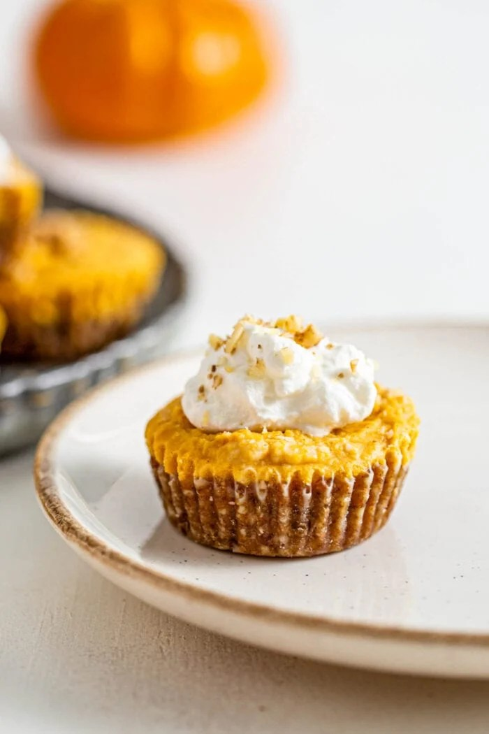 Mini pumpkin pie tart topped with whipped cream on a plate.