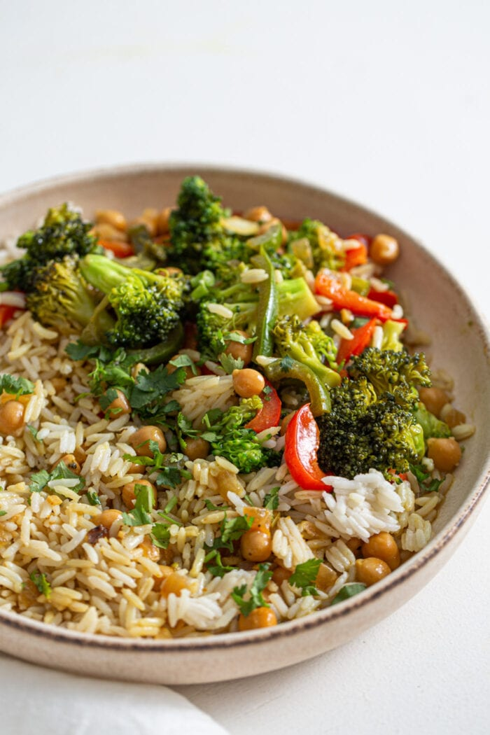 Bowl of rice, vegetables and chickpeas in a curry sauce.