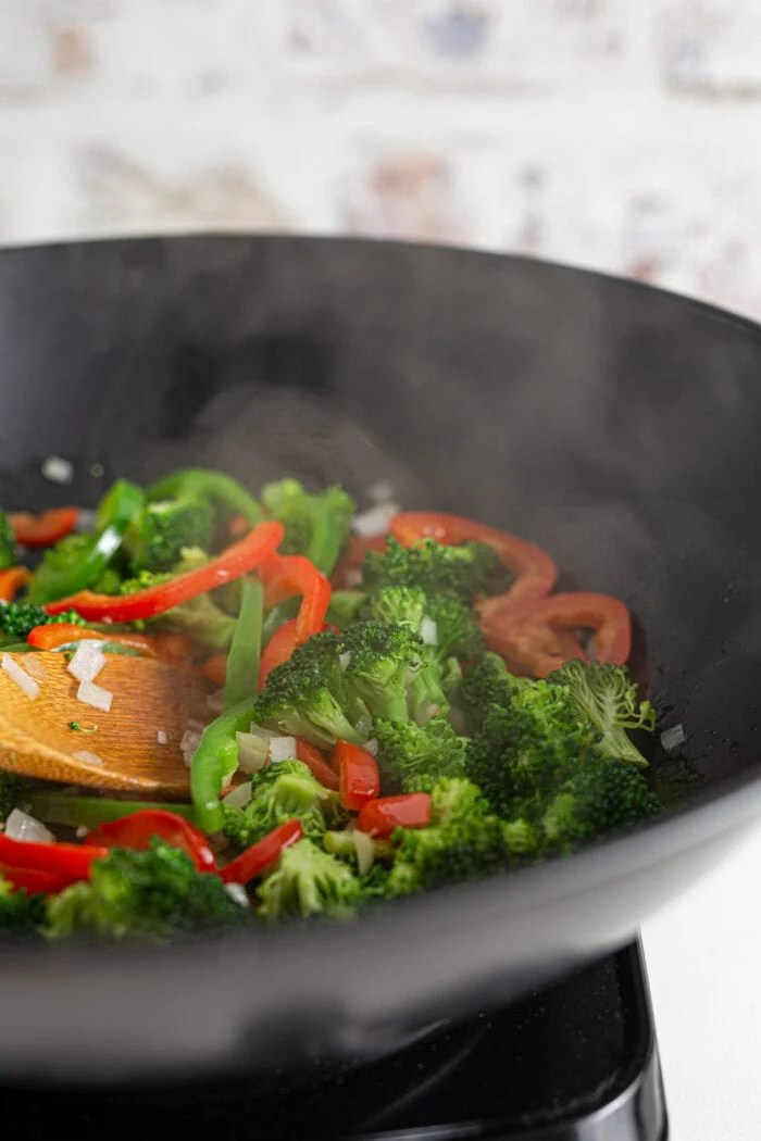 Broccoli and bell peppers cooking in hot wok with steam coming out of pan.