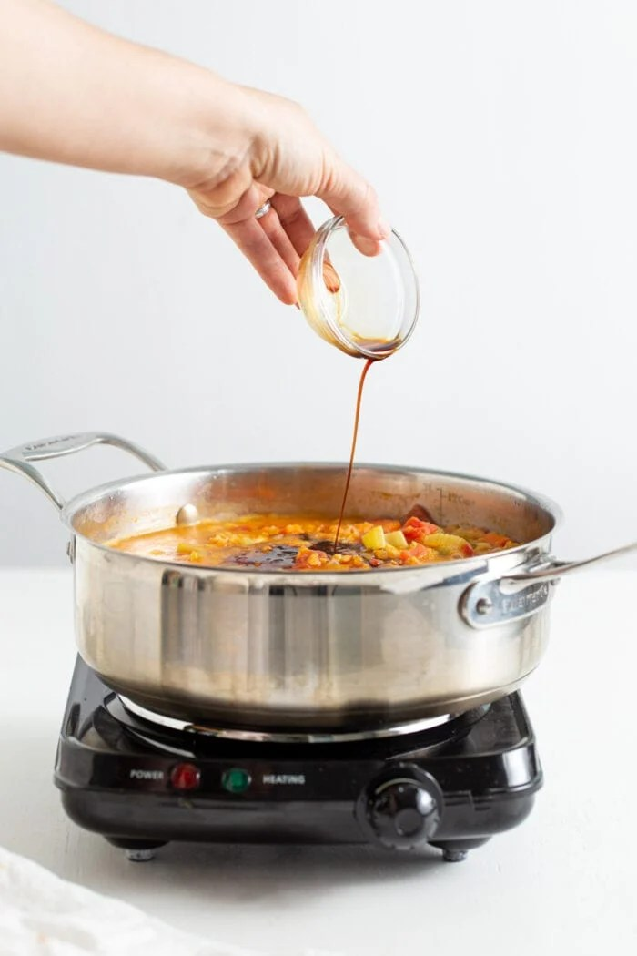 Pouring a small dish of soy sauce into a pot of soup.