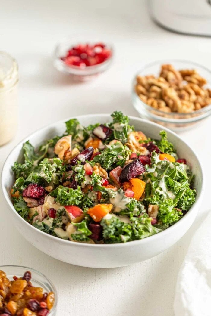 Bowl of kale salad with squash, beets, brussels sprouts, walnuts and pomegranate.