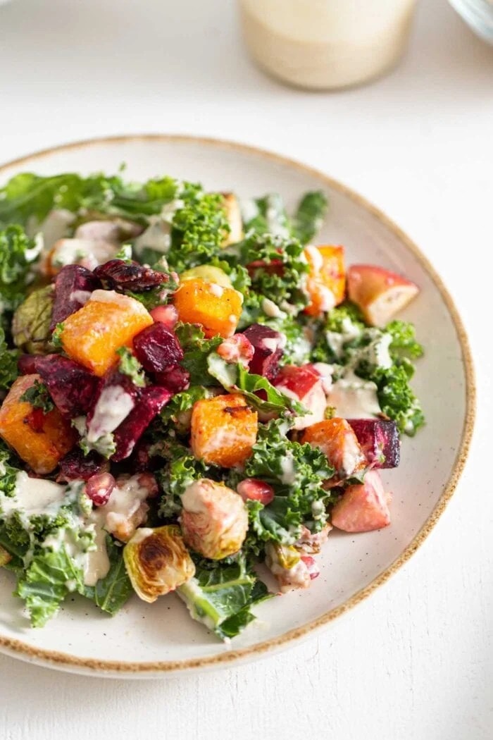 Colourful Fall salad with kale, roasted vegetables and tahini sauce on a plate.