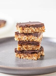 Stack of 4 chocolate coated cashew bars on a plate.