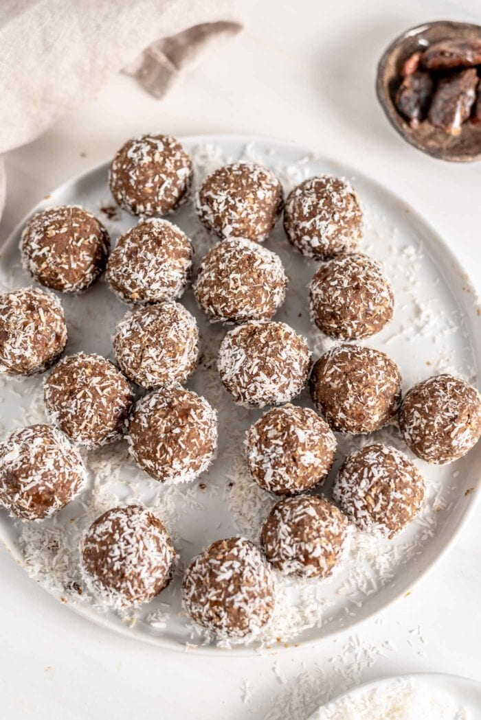 Overhead view of a plate of energy balls rolled in coconut.