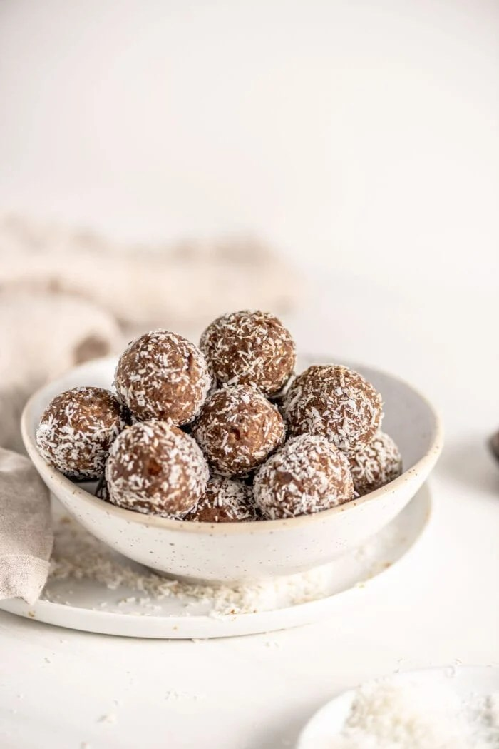 Bowl of protein balls rolled in coconut. Bowl sits on a plate, dish cloth in background.