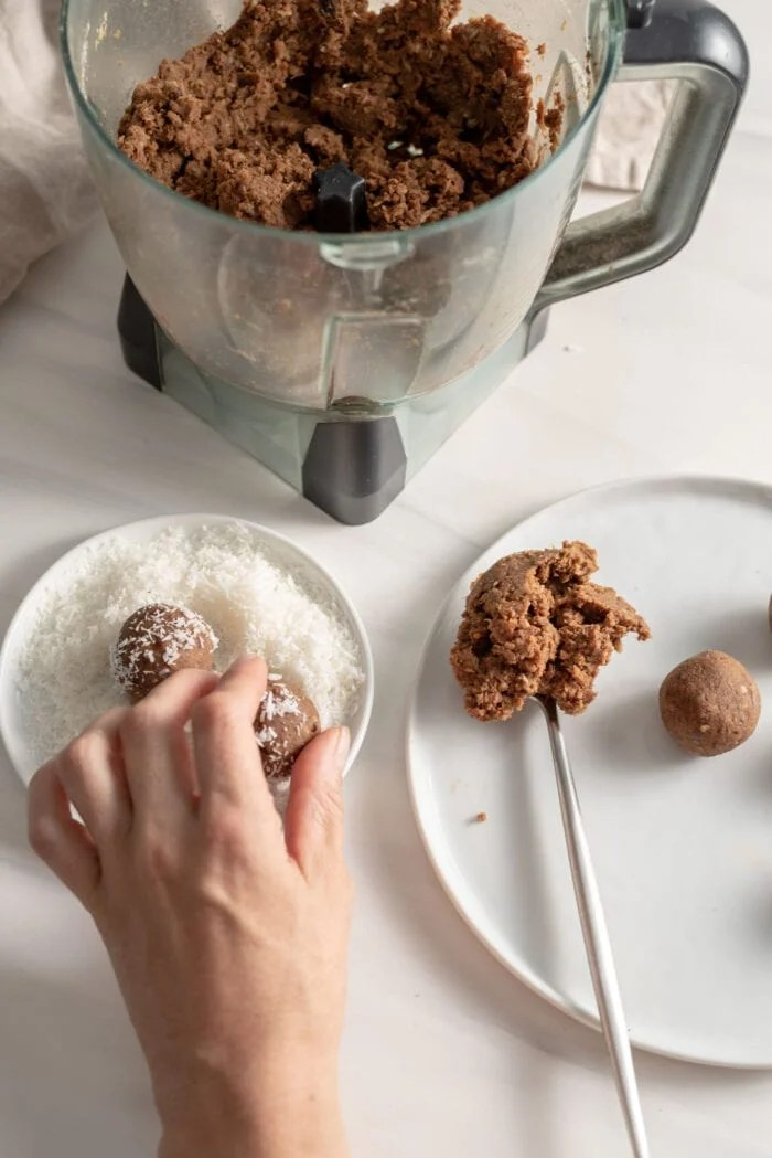 Hand rolling and energy ball in coconut on a small plate.