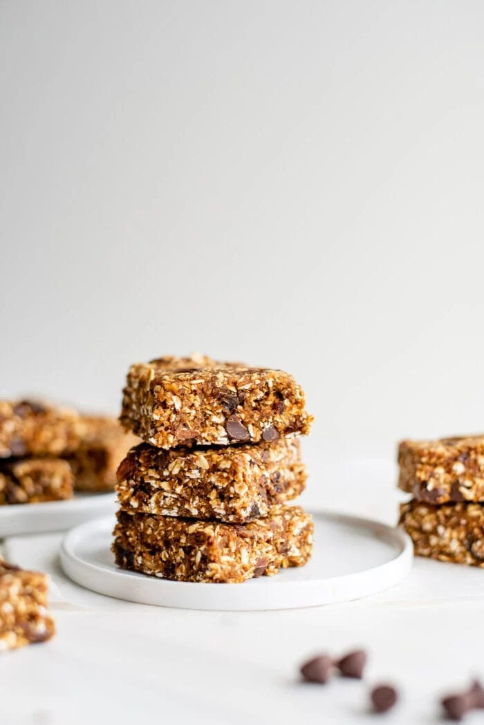 Stack of 3 oatmeal raisin chocolate chips bars on a plate. More bars in background.