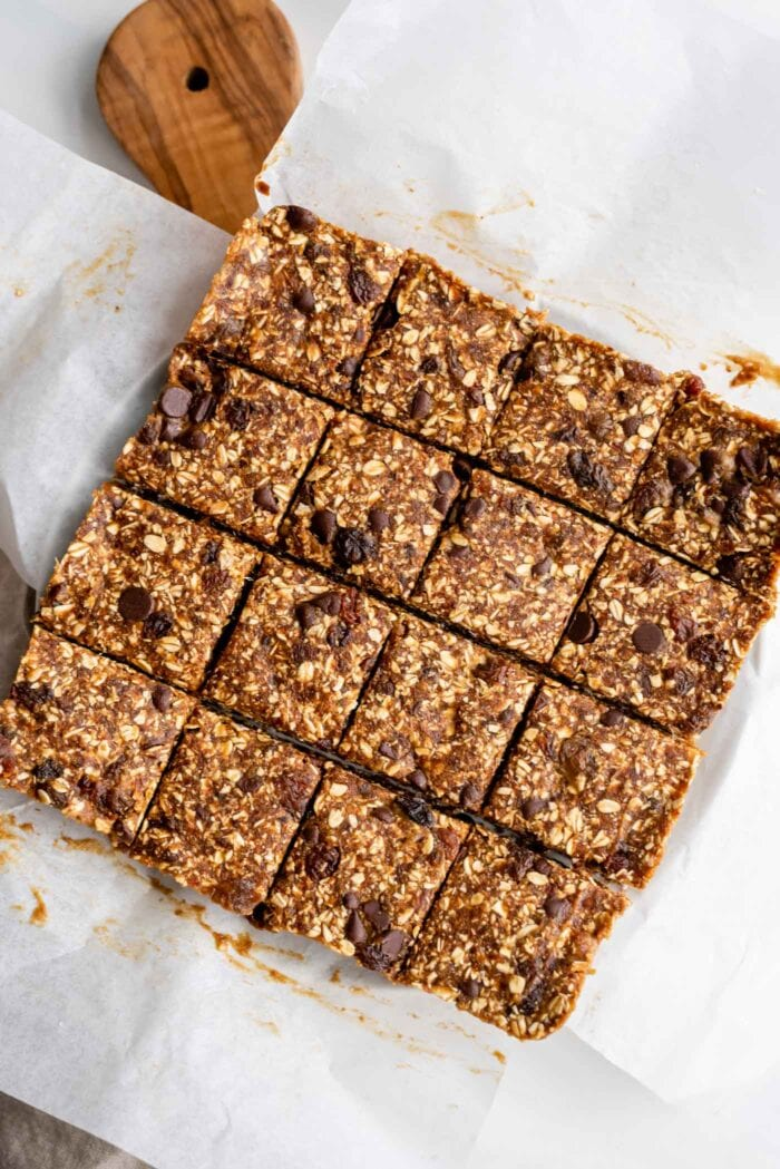 Overhead view of chocolate chip oatmeal bars sliced into 16 portions on a cutting board.