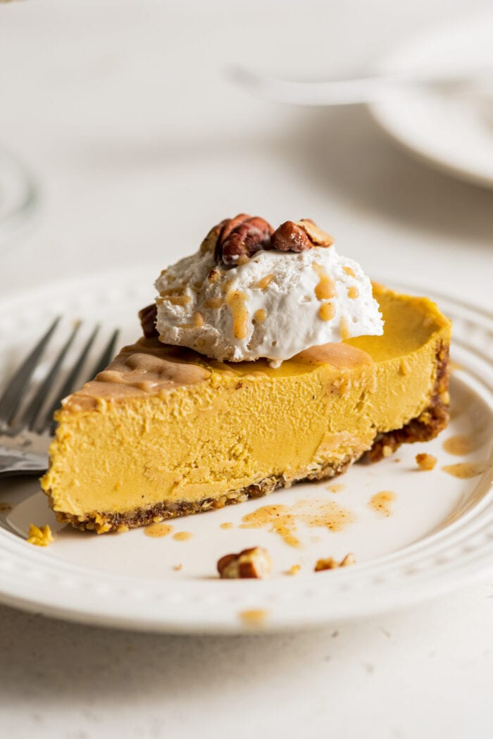 Slice of pumpkin cheesecake topped with whipped cream on a small plate. Fork rests on plate.