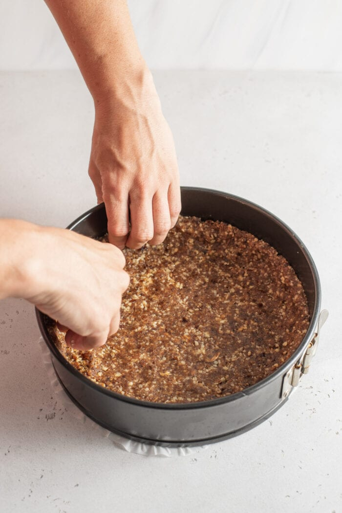 Hands working a doughy crust into a springform pan.