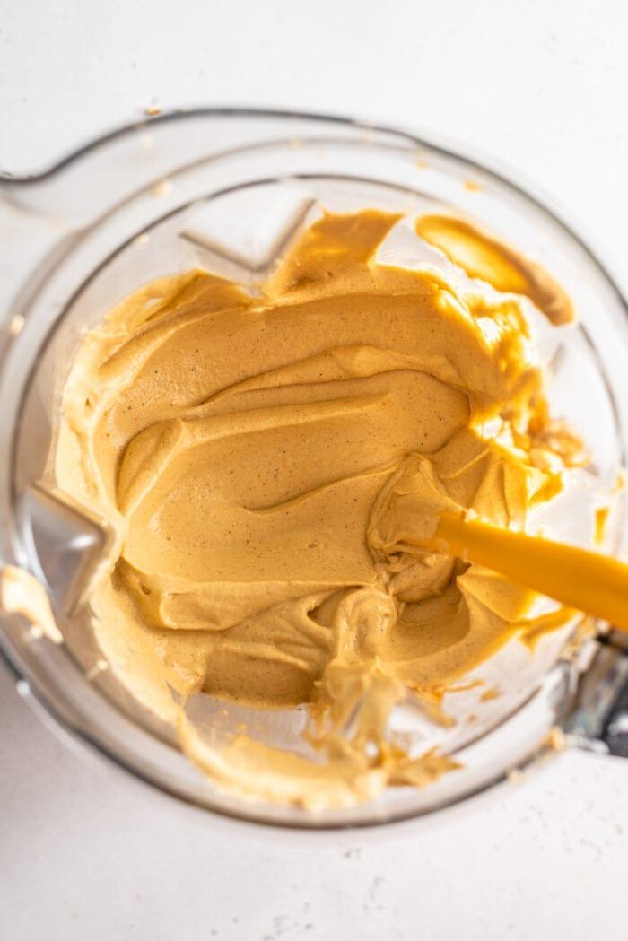 A creamy, smooth, orange mixture in a high-speed blender. Spatula rests in blender.