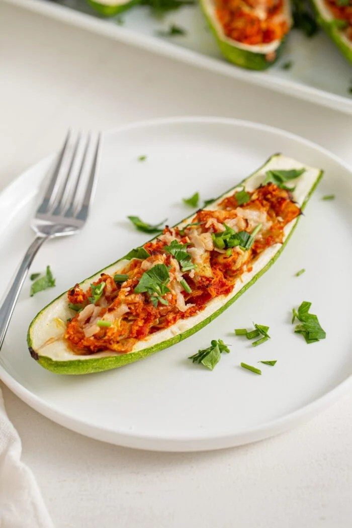 Half a zucchini on a plate stuffed with an artichoke and marinara sauce mixture. Fork rests on plate.