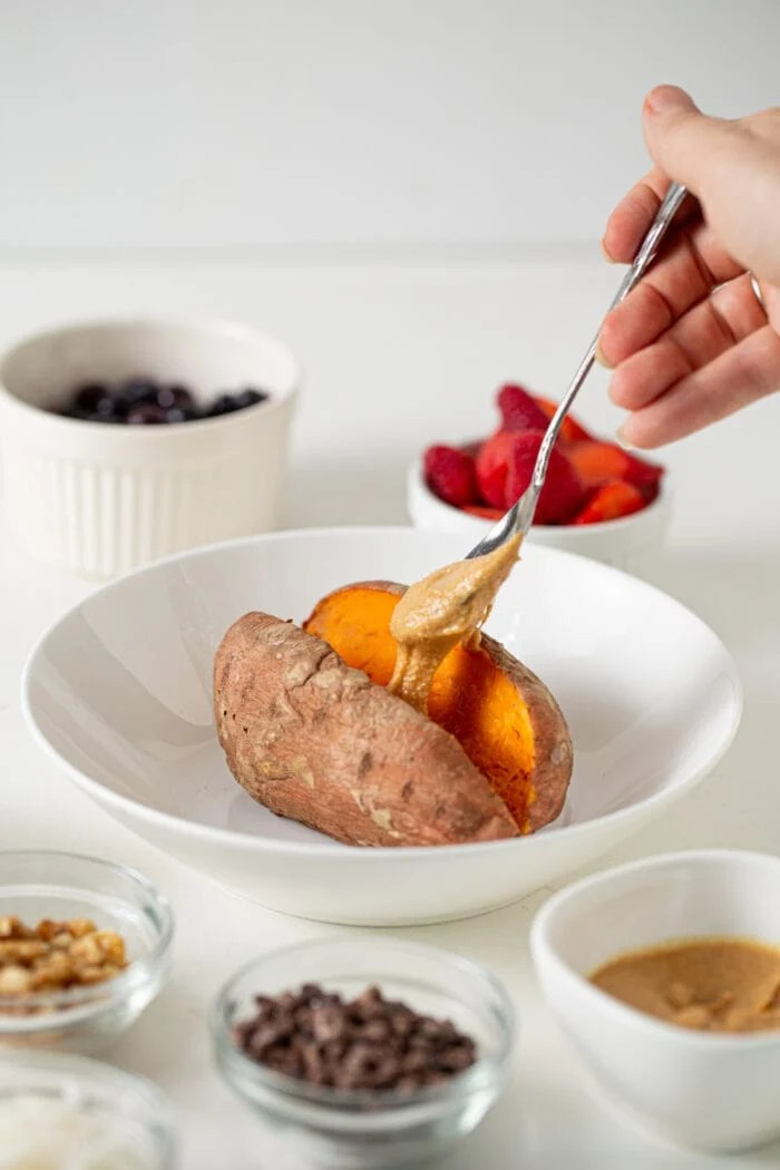 Hand adding a spoonful of peanut butter to a baked sweet potato in a bowl.