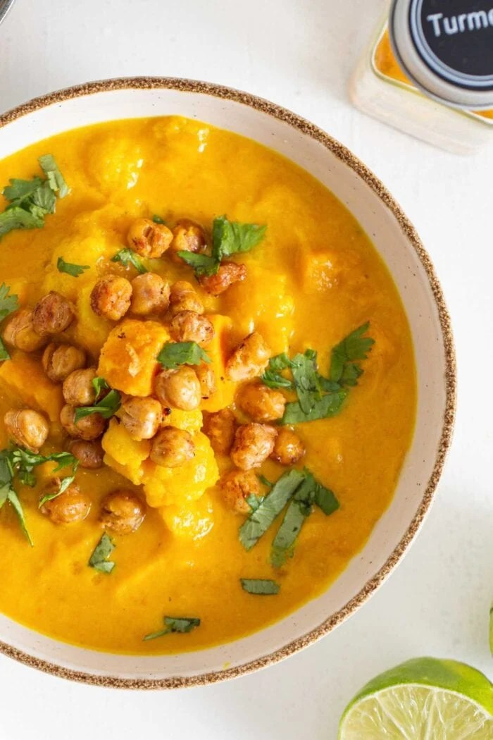 Overhead view of a bowl of chunky sweet potato cauliflower soup topped with chickpeas and cilantro.