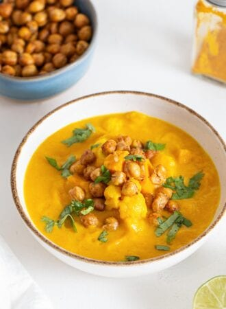 Bowl of sweet potato cauliflower soup topped with chickpeas and cilantro.