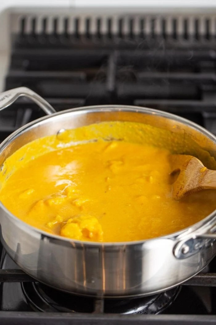 Pot of creamy sweet potato soup cooking on gas range stove. Wooden spoon rests in pot.
