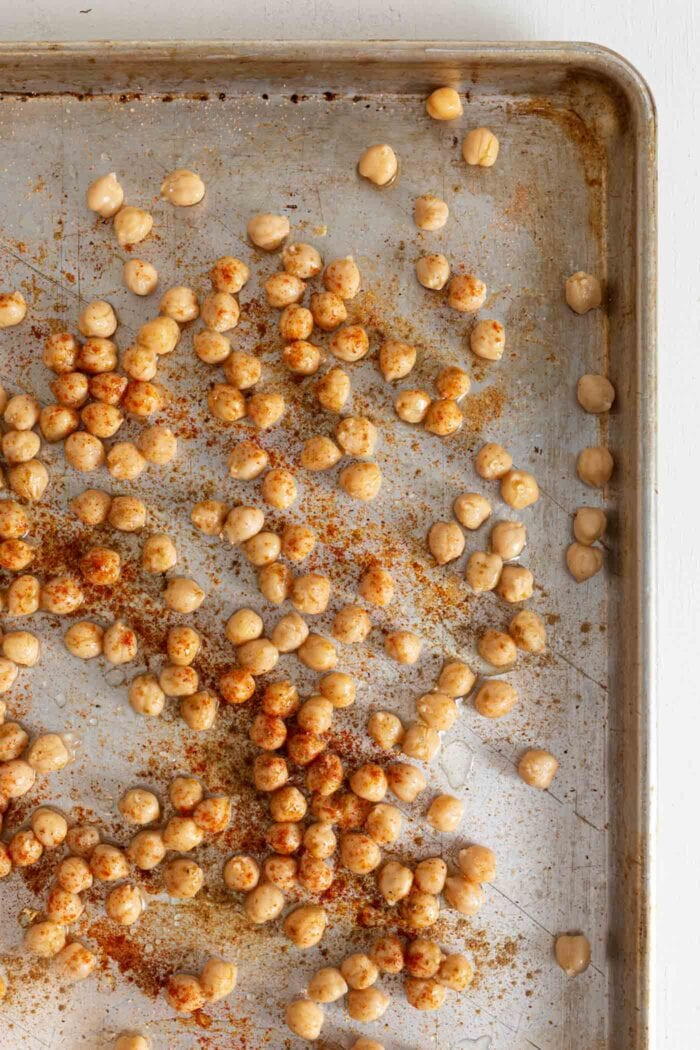 Overhead view of chickpeas on a pan tossed with spices.