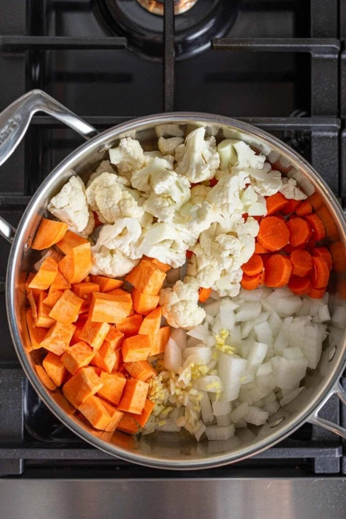 Sweet potato, cauliflower, carrot and onion cooking in a stock pot on a gas range stovetop.