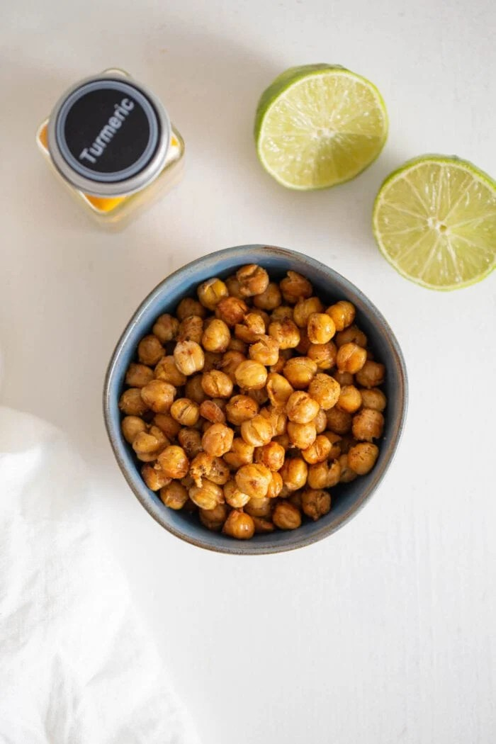 Overhead view of a bowl or roasted chickpeas. Cut open lime beside it.