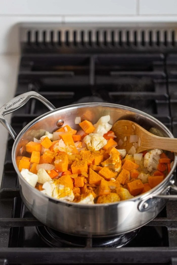 Sweet potato, cauliflower, carrot, onion and turmeric cooking in a stock pot on a gas range stovetop.