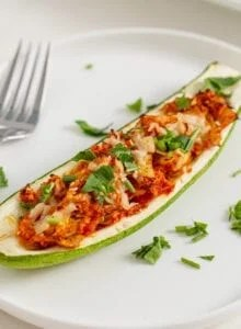 Stuffed zucchini boat topped with cheese and herbs on a plate. Fork rests on plate.