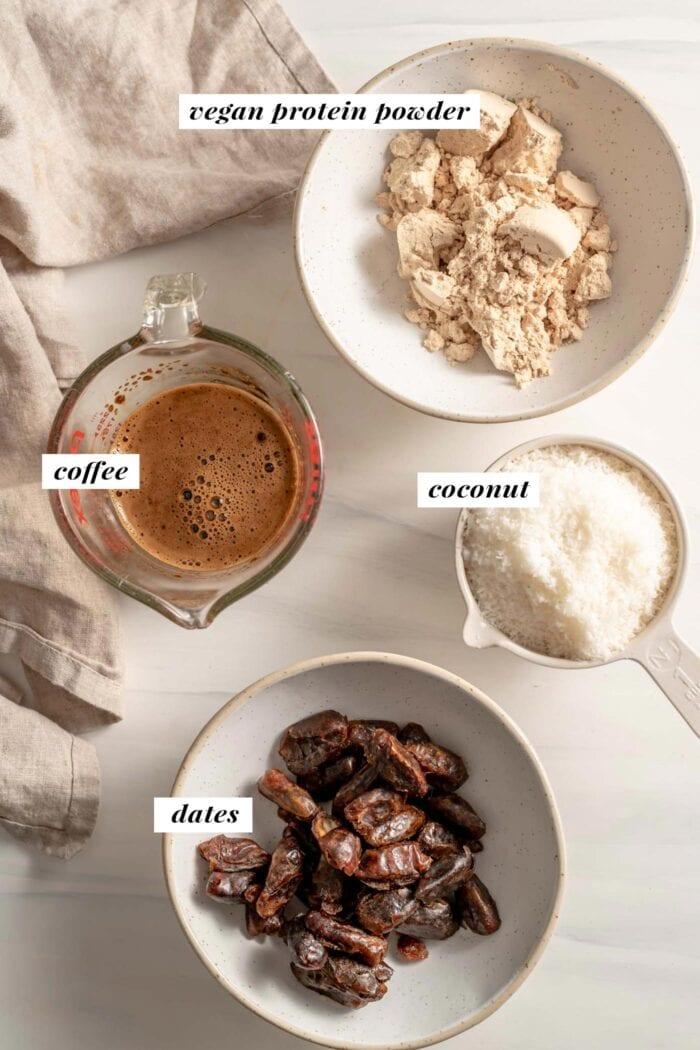 Dates, coffee, coconut and protein powder in bowls. Each ingredient is labelled with text overlay.