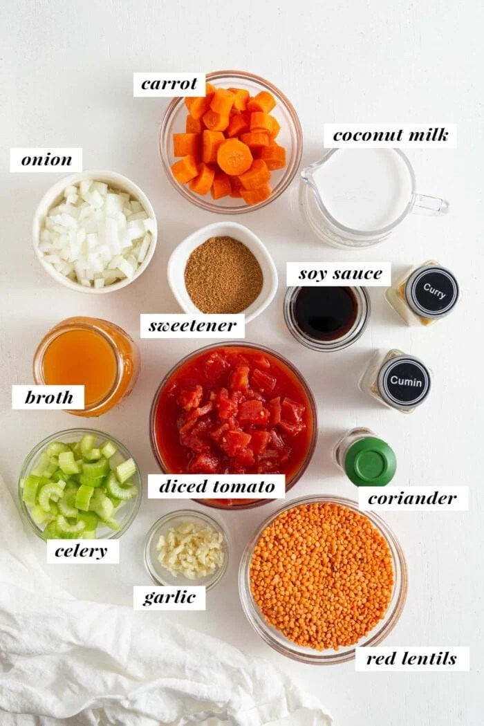 Overhead view of labelled ingredients needed for making a curried red lentil soup.