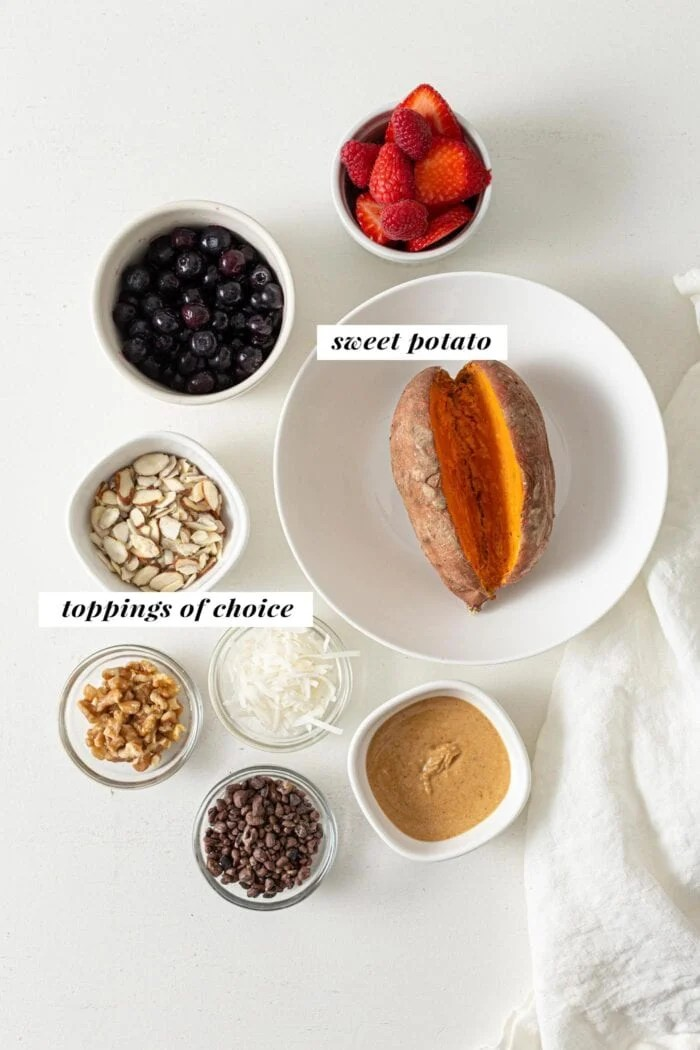 Overhead view of sweet potato, peanut butter, berries, coconut, cacao nibs and almonds in small dishes.