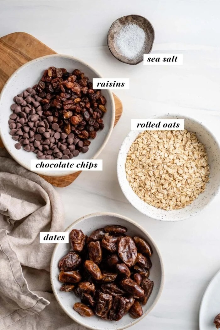 Overhead view of dates, oats, chocolate chips and raisins in bowls. Each bowl is labelled with text overlay.
