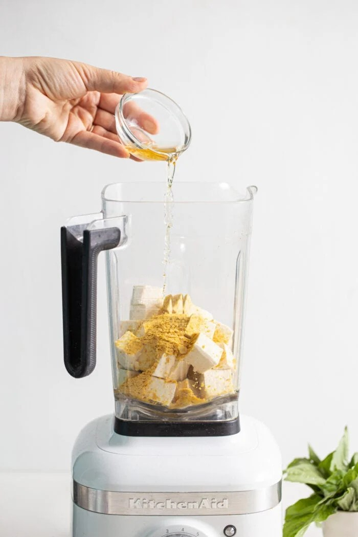 Pouring a small dish of vinegar into a blender with tofu and nutritional yeast.