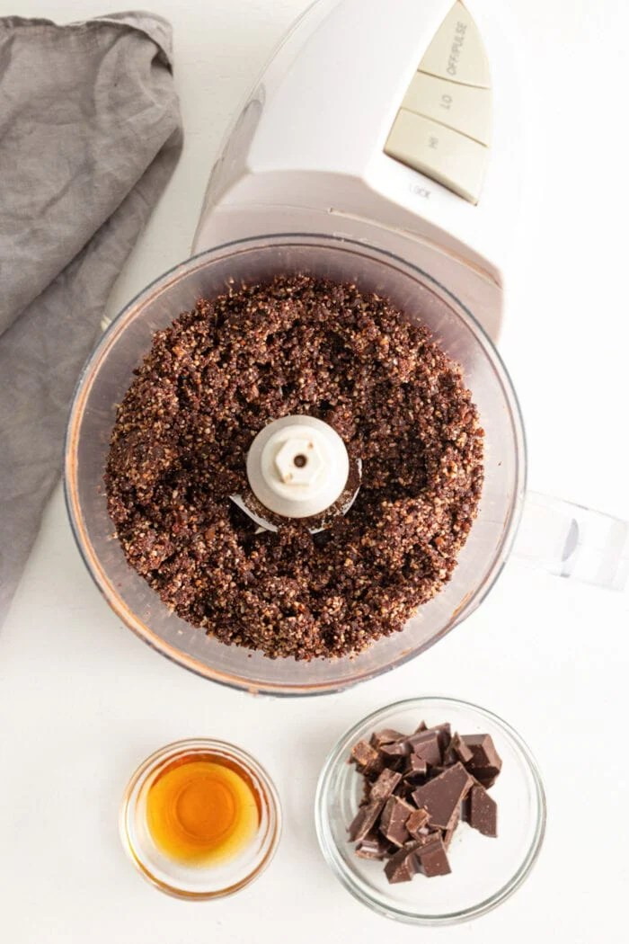 Dates blended with cocoa powder and pecans in a food processor. Small dish of chocolate beside food processor.