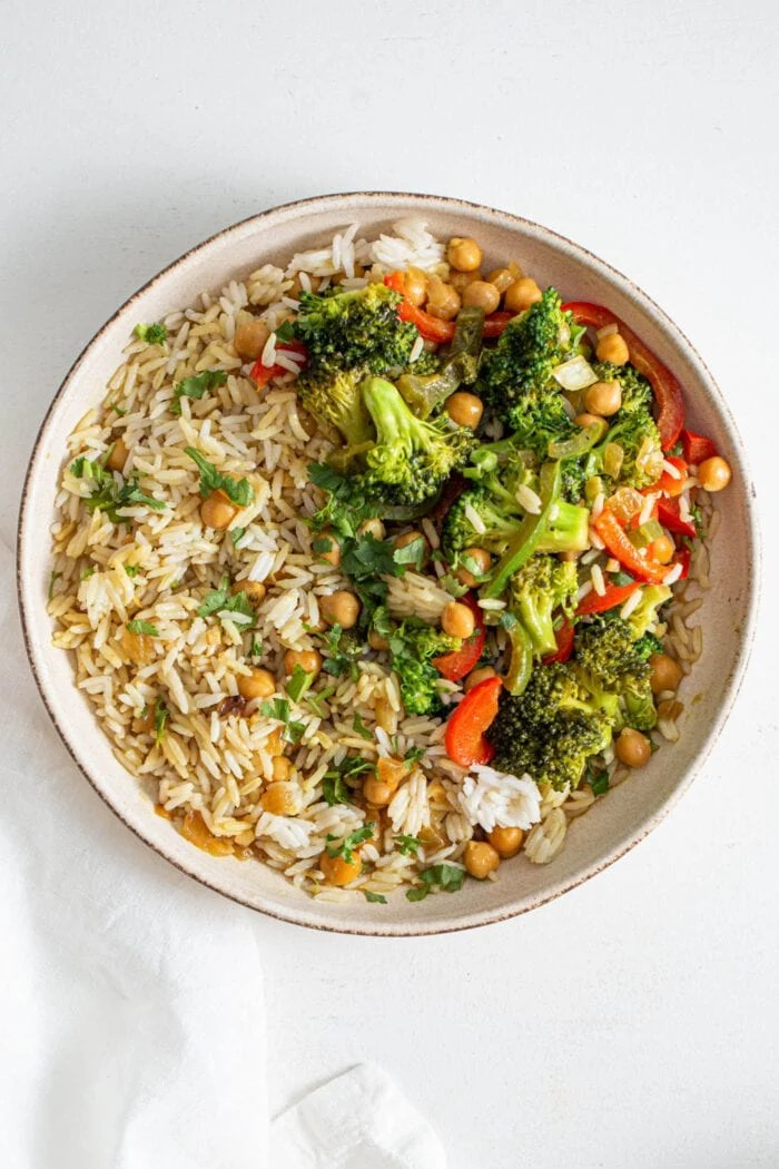 Overhead view of a bowl of rice with chickpeas and vegetables.