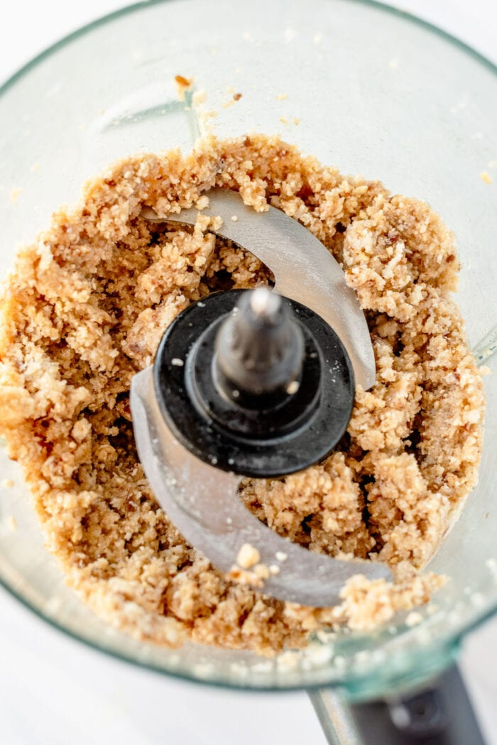 Crumbly dough made of dates, coconut and cashews in a food processor.