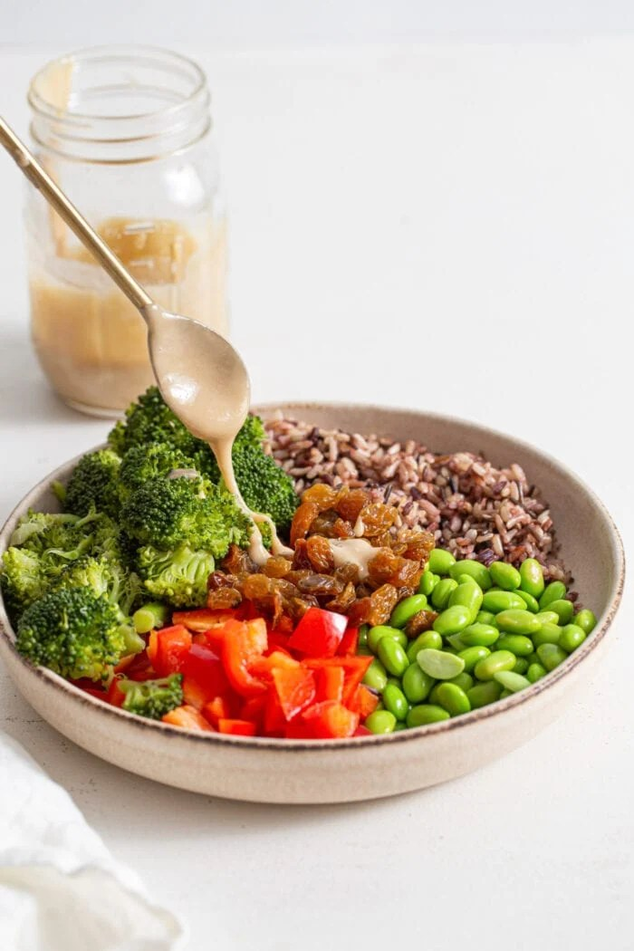 Drizzling a spoonful of tahini dressing over a large bowl of chopped vegetables, edamame and wild rice.