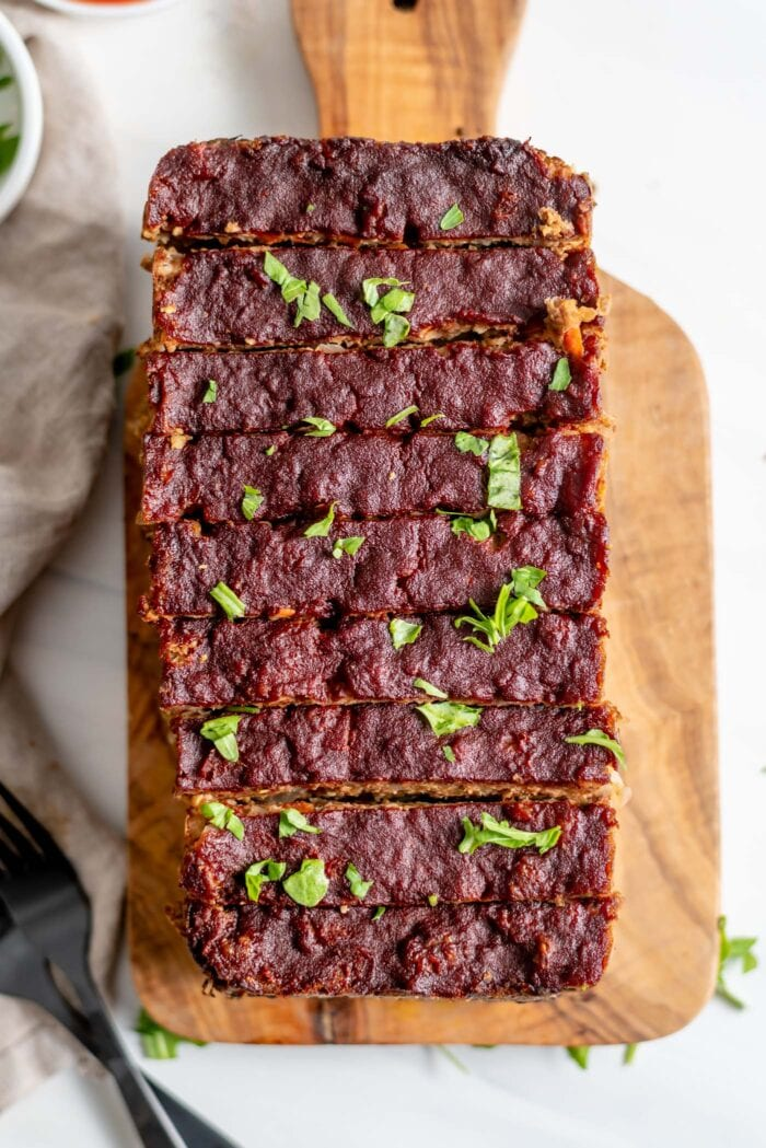 Overhead view of a vegetarian meatloaf cut into slices on a cutting board.