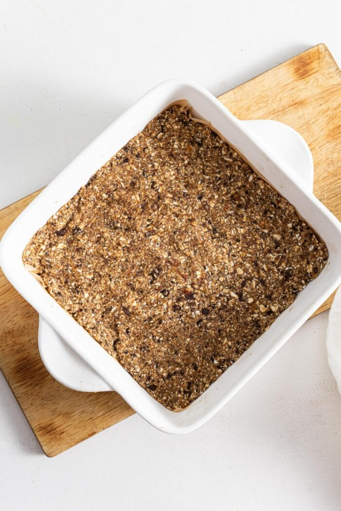 Energy bars in a ceramic baking dish with handles, sitting on a cutting board.