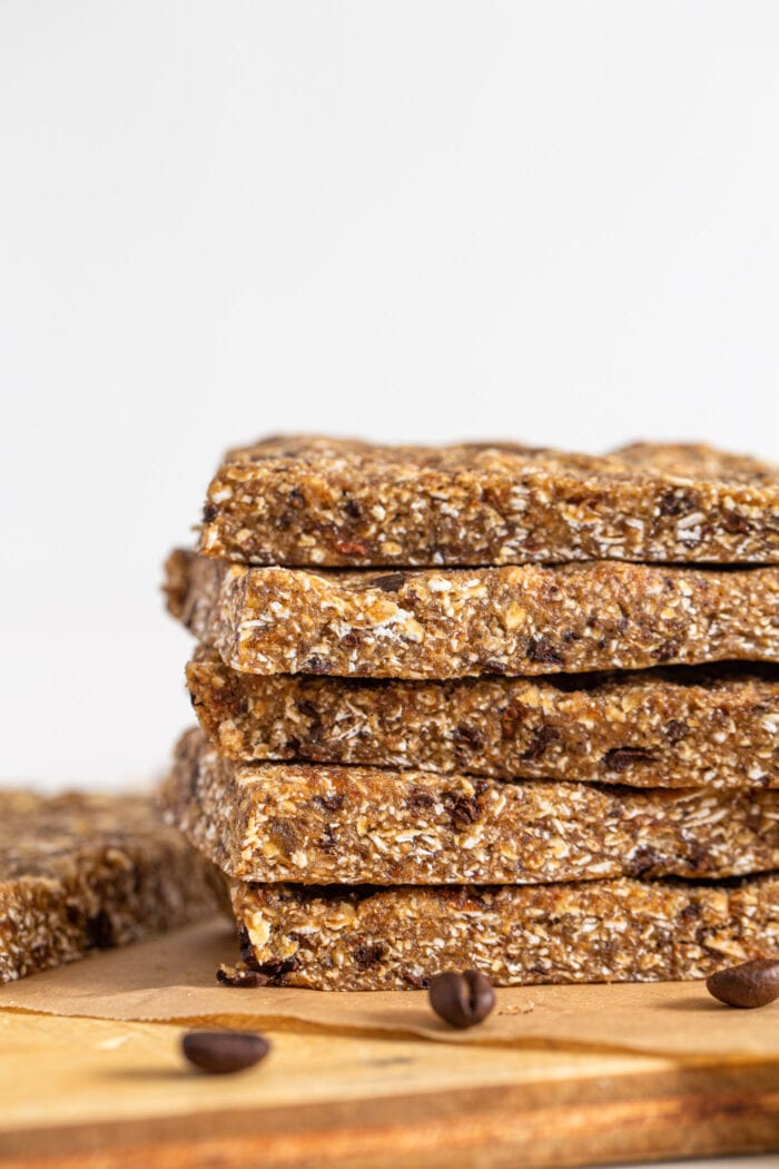 Close up of a stack of 5 energy bars with coffee beans in them. Bars sit on a cutting board.