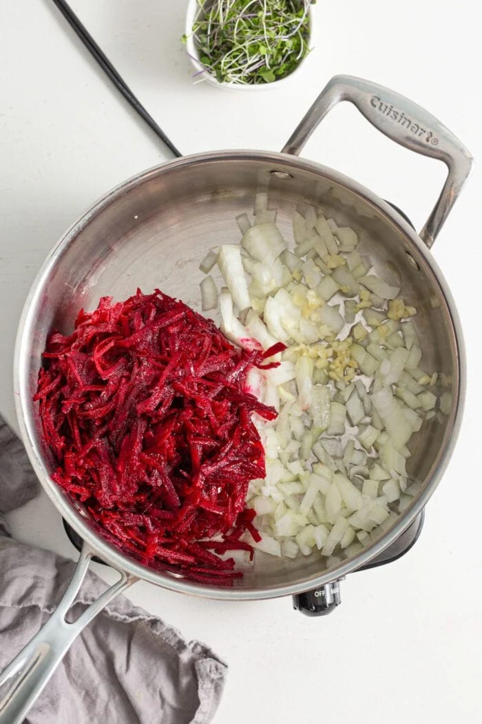 Cooking grated beets, onions and garlic in a pan.
