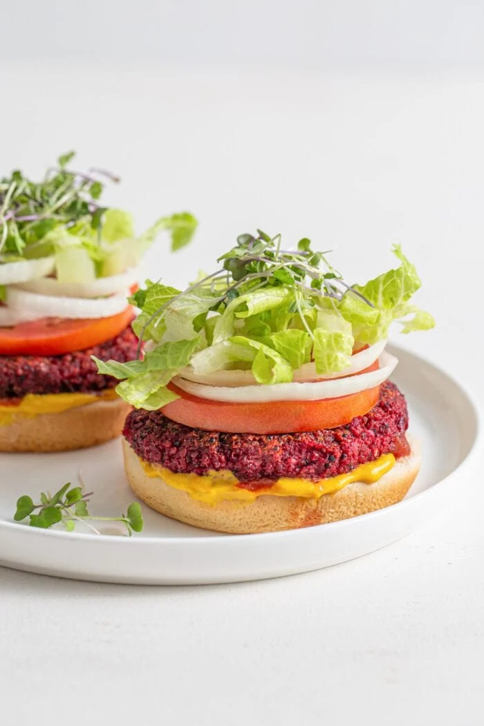 Two beetroot burgers on buns with lettuce, sprouts, tomato, onion, mustard and ketcup.