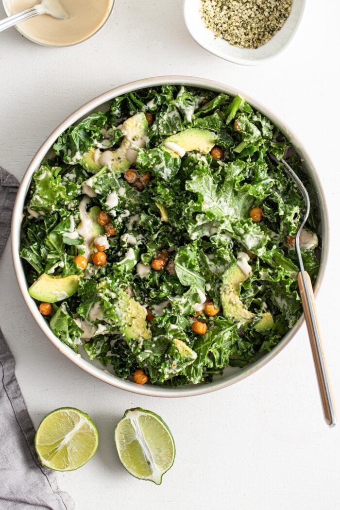 Overhead view of a bowl of kale salad with chickpeas, avocado and hemp seeds.