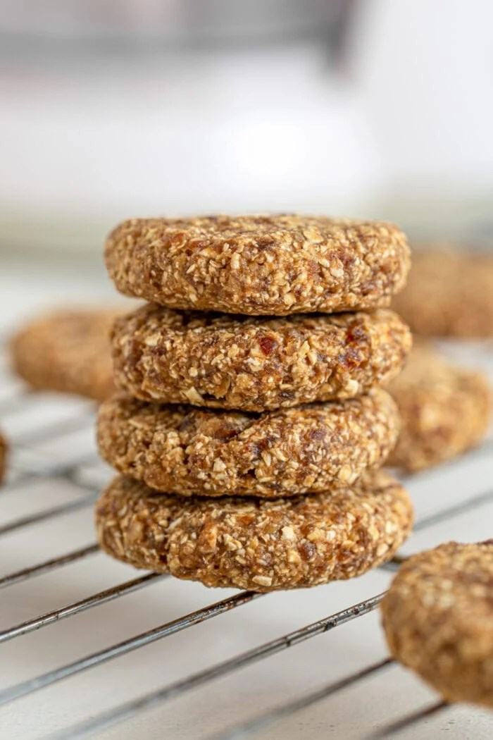 Stack of 4 tahini date cookies sitting on a cooling rack.